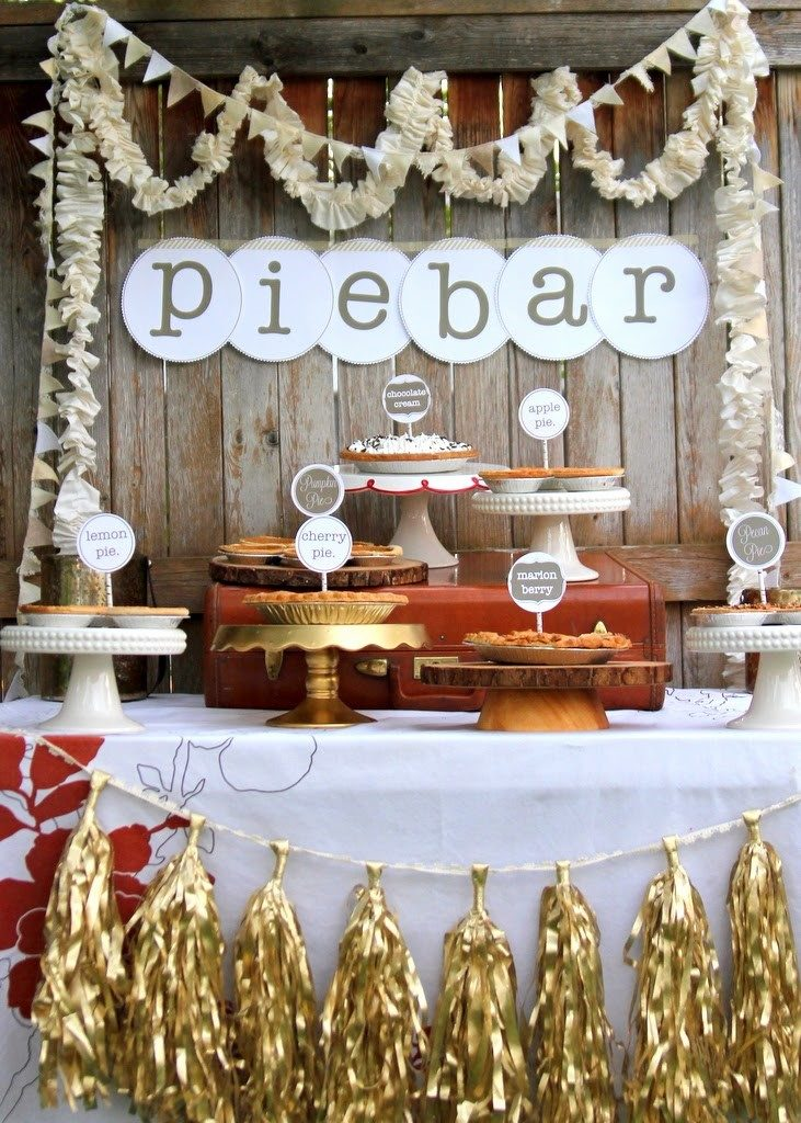 This photo features a pie bar with a variety of flavors on serving trays with different heights. The pie bar table is decorated with fun garland and a large sign that reads pie bar. Each individual pie has a sign in it to indicate flavor.