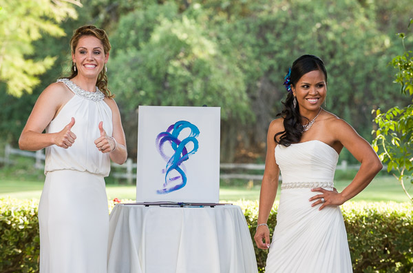 This photo features two brides posing with their unity painting.